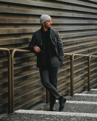 How to wear: grey beanie, black leather derby shoes, black crew-neck sweater, charcoal vertical striped suit