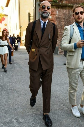 How to Wear a Dark Brown Suit In a Dressy Way: This sophisticated pairing of a dark brown suit and a light blue dress shirt is a frequent choice among the dapper gentlemen. To give your overall getup a more laid-back spin, why not complete this ensemble with a pair of black leather derby shoes?
