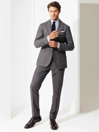 How to Wear a Grey Wool Suit: You'll be amazed at how extremely easy it is to pull together this elegant look. Just a grey wool suit and a light blue dress shirt. Bring an easy-going vibe to your look by finishing with dark purple leather derby shoes.