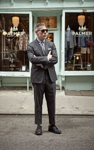 Men's Looks & Outfits: What To Wear In 2020: A charcoal suit and a light blue dress shirt are absolute staples if you're putting together a stylish wardrobe that holds to the highest sartorial standards. A pair of black leather derby shoes will bring a casual aesthetic to the ensemble.