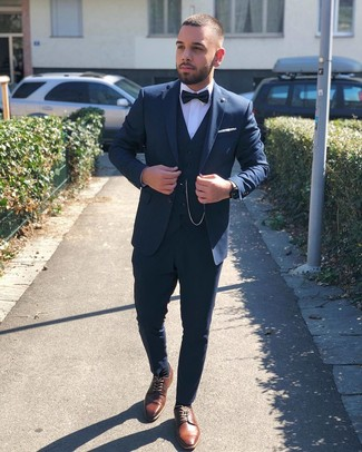 How to Wear a Navy Three Piece Suit: Channel your inner British gentleman and try teaming a navy three piece suit with a white dress shirt. To give your overall look a more laid-back aesthetic, why not complete your look with a pair of brown leather derby shoes?