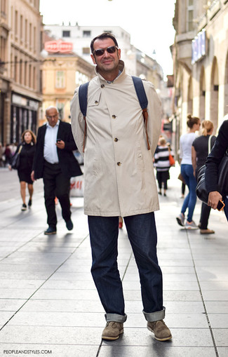 How to wear: black leather backpack, olive suede desert boots, navy jeans, beige raincoat