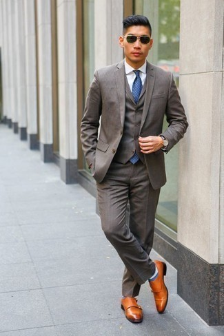 How to Wear a Blue Polka Dot Tie For Men: Combining a grey three piece suit and a blue polka dot tie is a fail-safe way to infuse your wardrobe with some masculine sophistication. A pair of tobacco leather double monks will bring a laid-back feel to this look.