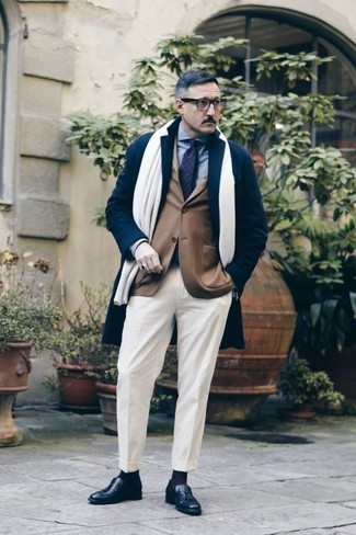 How to Wear White Dress Pants For Men: Rock a navy overcoat with white dress pants for classy style with a modern twist. Complement your look with a pair of black leather tassel loafers to make a dressy outfit feel suddenly edgier.