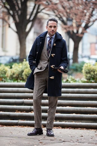 Men's Looks & Outfits: What To Wear In Winter: To look like a stylish dandy at all times, pair a navy duffle coat with a brown wool suit. Serve a little outfit-mixing magic by rounding off with a pair of dark purple leather brogue boots. A practical example of comfortable style, this look must be in your wardrobe this winter.
