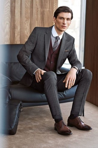 How to Wear a Charcoal Check Suit: This combination of a charcoal check suit and a burgundy sweater vest can only be described as outrageously dapper and sophisticated. A pair of brown leather brogues immediately ramps up the style factor of your getup.