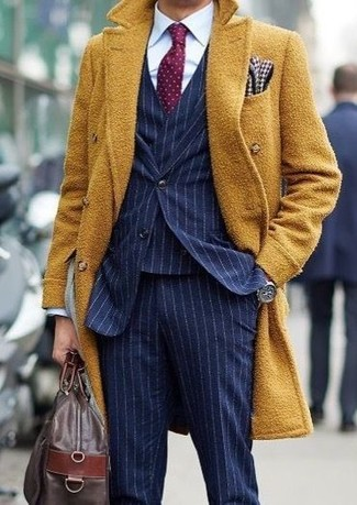 How to wear: dark brown leather holdall, white dress shirt, navy vertical striped three piece suit, mustard overcoat