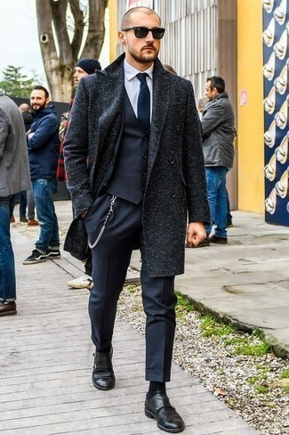 How to Wear a Navy Three Piece Suit: Combining a navy three piece suit and a navy overcoat is a surefire way to infuse your styling rotation with some rugged elegance. Puzzled as to how to finish off? Introduce black leather double monks to the equation for a more casual touch.