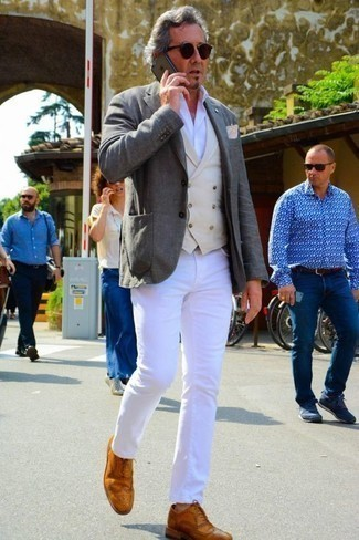How to Wear a Beige Waistcoat: We love how this combination of a beige waistcoat and white jeans instantly makes a man look smart and classy. Throw tobacco leather brogues in the mix and you're all done and looking incredible.
