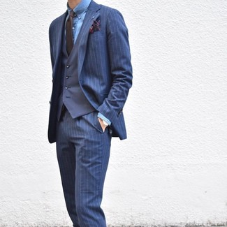 How to wear: dark brown tie, blue chambray dress shirt, navy waistcoat, navy vertical striped suit