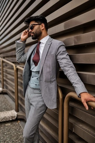 How to wear: burgundy print tie, white dress shirt, grey waistcoat, grey vertical striped suit