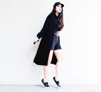 Rock a black duster coat with black shorts for an unexpectedly cool ensemble. Complement this look with black leather slip-on sneakers.