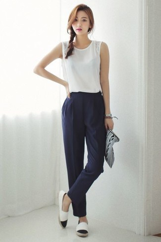 How to wear: black and white print leather clutch, white and black espadrilles, navy tapered pants, white sleeveless top