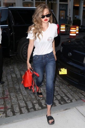 How to wear: red leather backpack, black leather flat sandals, navy skinny jeans, white print v-neck t-shirt