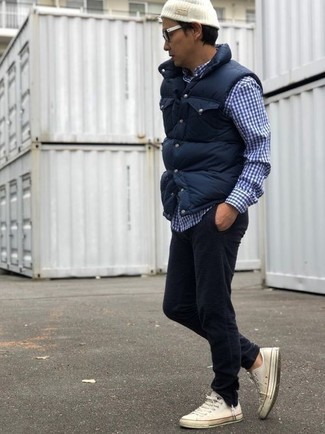 How to wear: navy quilted gilet, navy and white gingham long sleeve shirt, black corduroy jeans, white canvas low top sneakers