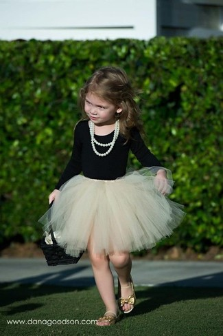 How to Wear Gold Sandals For Girls: Suggest that your little one pair a black long sleeve t-shirt with a beige tulle skirt for a glam and trendy getup. This getup is complemented nicely with gold sandals.