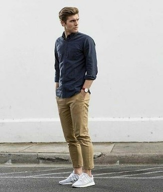 How to Wear a Navy Long Sleeve Shirt For Men: The ultimate choice for a kick-ass casual outfit for men? A navy long sleeve shirt with khaki chinos. Avoid looking overdressed by finishing with a pair of grey athletic shoes.