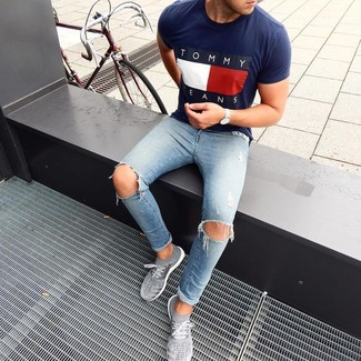 How to Wear Grey Athletic Shoes For Men: This modern casual pairing of a navy print crew-neck t-shirt and light blue ripped skinny jeans can go in different directions depending on how it's styled. The whole ensemble comes together when you complete this getup with a pair of grey athletic shoes.