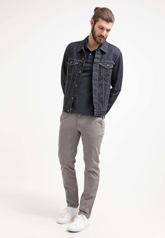 How to wear: white low top sneakers, grey chinos, black polo, navy denim jacket