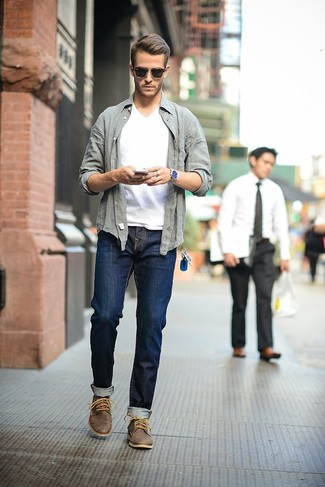 This combo of a grey long sleeve shirt and navy blue jeans will enable you to keep your off-duty style clean and simple. Finish off this look with dark brown leather desert boots.