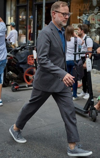 How to Wear Grey Canvas Low Top Sneakers For Men: This is hard proof that a charcoal suit and a blue denim shirt look awesome when you pair them in a sophisticated ensemble for a modern guy. Grey canvas low top sneakers are an easy way to add a hint of stylish nonchalance to your getup.