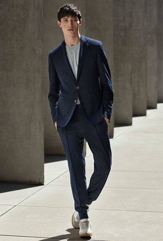 How to wear: grey suede low top sneakers, grey crew-neck t-shirt, navy suit