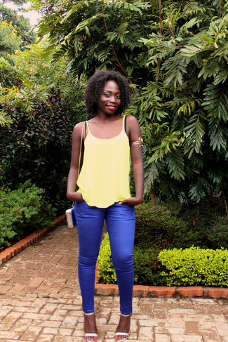 How to Wear a Blue Leather Crossbody Bag: You'll be amazed at how easy it is to get dressed like this. Just a yellow tank paired with a blue leather crossbody bag. You can get a little creative on the shoe front and complete this outfit with a pair of silver leather heeled sandals.