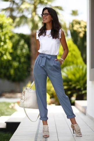How to wear: white leather satchel bag, beige fringe suede heeled sandals, blue tapered pants, white ruffle sleeveless top