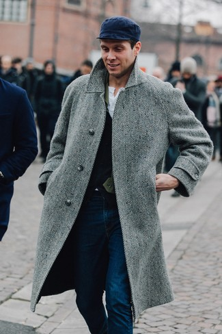 How to Wear a Navy Flat Cap For Men: We're all on the lookout for practicality when it comes to fashion, and this relaxed casual pairing of a grey herringbone overcoat and a navy flat cap is a practical illustration of that.