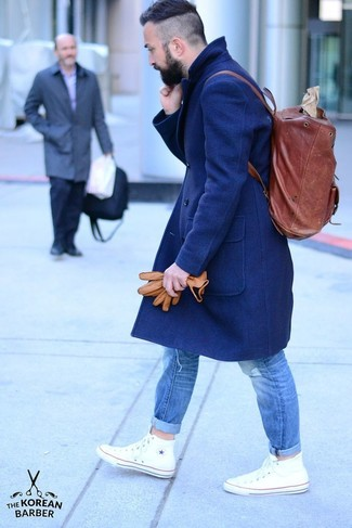 How to wear: burgundy leather backpack, white high top sneakers, blue ripped jeans, navy overcoat