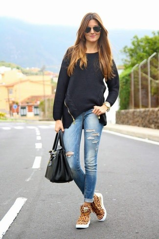 How to Wear a Black Oversized Sweater: This combo of a black oversized sweater and blue ripped skinny jeans is extremely versatile and apt for whatever the day throws at you. Add a pair of tan leopard high top sneakers to the mix and the whole getup will come together brilliantly.