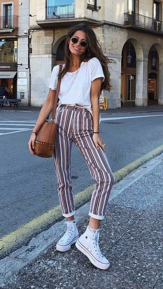 How to wear: brown leather crossbody bag, white canvas high top sneakers, white and red vertical striped skinny pants, white crew-neck t-shirt