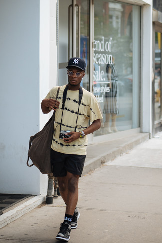 How to wear: dark brown canvas tote bag, black leather high top sneakers, black sports shorts, yellow tie-dye crew-neck t-shirt