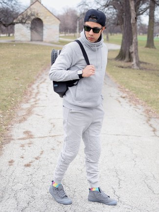How to wear: charcoal canvas backpack, grey high top sneakers, grey sweatpants, grey hoodie