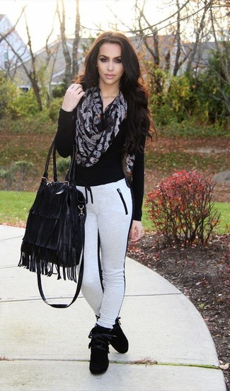 How to wear: black fringe leather tote bag, black suede high top sneakers, white and black sweatpants, black v-neck sweater