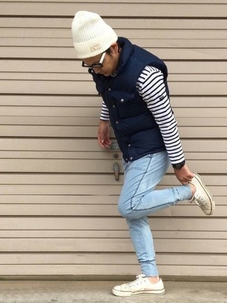 How to wear: white low top sneakers, light blue jeans, white and navy horizontal striped crew-neck sweater, navy quilted gilet