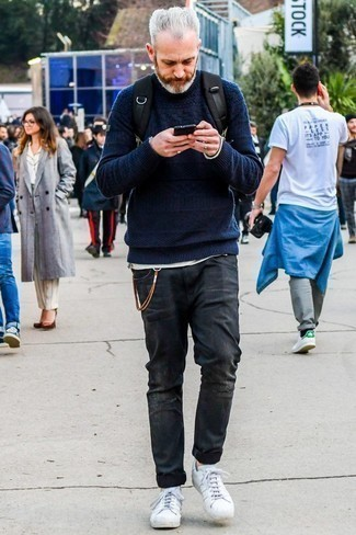 How to Wear Charcoal Ripped Jeans For Men: This pairing of a navy cable sweater and charcoal ripped jeans spells comfort without compromising style. White leather low top sneakers will infuse a touch of refinement into an otherwise mostly casual ensemble.