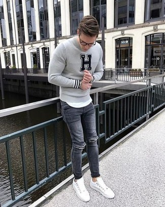 Men's Looks & Outfits: What To Wear In Spring: Dress in a grey print crew-neck sweater and grey ripped jeans for a casual level of dress. To add some extra definition to this getup, complement this ensemble with white canvas low top sneakers. So as you can see, it's a sharp, not to mention spring-friendly, getup to keep in your transitional arsenal.