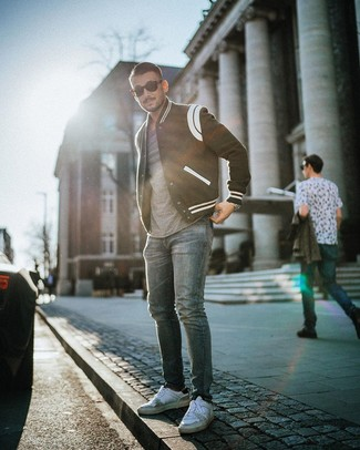 How to wear: white leather low top sneakers, blue jeans, grey crew-neck t-shirt, black and white varsity jacket