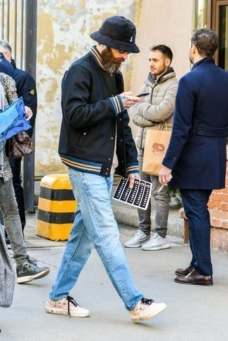Fashion for Men Over 40: What To Wear: A black varsity jacket and light blue jeans are essential in any man's functional off-duty closet. Make pink low top sneakers your footwear choice for extra style points.