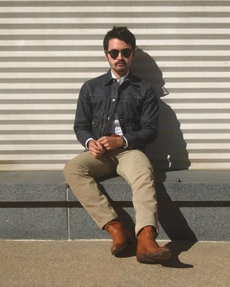 How to Wear a Navy Denim Jacket For Men: A navy denim jacket and beige jeans are the perfect way to inject toned down dapperness into your casual arsenal. To bring a more casual touch to this ensemble, throw a pair of brown leather cowboy boots in the mix.