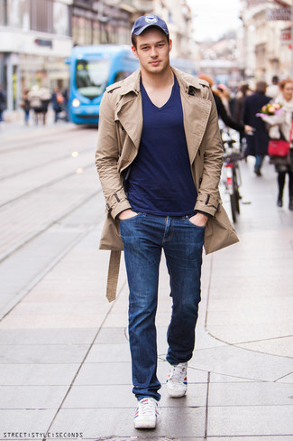 How to wear: white and red and navy horizontal striped low top sneakers, navy jeans, navy v-neck t-shirt, tan trenchcoat