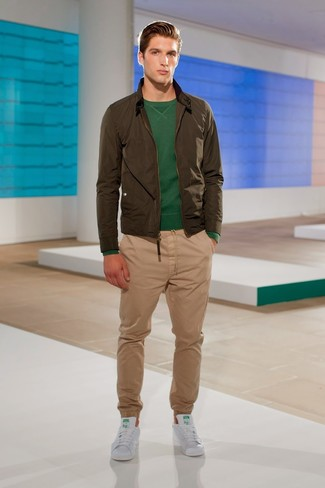 How to wear: white leather low top sneakers, khaki chinos, dark green crew-neck sweater, olive bomber jacket