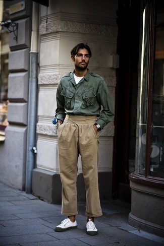 How to Wear a Dark Green Military Jacket For Men: This off-duty combination of a dark green military jacket and khaki chinos can only be described as outrageously sharp. Loosen things up and introduce white canvas low top sneakers to the equation.