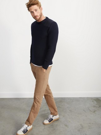 Men's Looks & Outfits: What To Wear In 2020: Go for casual and cool style in a navy crew-neck sweater and khaki chinos. White and navy leather low top sneakers are a surefire way to bring a dash of stylish nonchalance to this outfit.