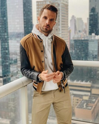 How to wear: brown leather watch, khaki chinos, white hoodie, brown bomber jacket
