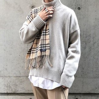 How to Wear a Beige Knit Turtleneck For Men: Teaming a beige knit turtleneck with khaki dress pants is a smart choice for a smart and refined getup.