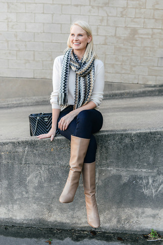 How to wear: black quilted leather satchel bag, tan leather knee high boots, navy skinny jeans, white crew-neck sweater