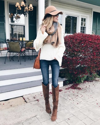 How to Wear Brown Suede Knee High Boots: For comfort without the need to sacrifice on good style, we turn to this combination of a white knit oversized sweater and navy skinny jeans. You can get a bit experimental on the shoe front and lift up this ensemble by rocking brown suede knee high boots.