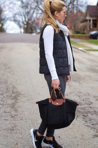How to wear: black athletic shoes, charcoal leggings, white crew-neck sweater, black quilted gilet